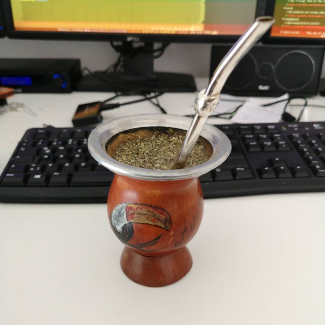 Yerba Mate with Bombilla in a gourd with a depiction of a Toucan on the table in front of the keyboard